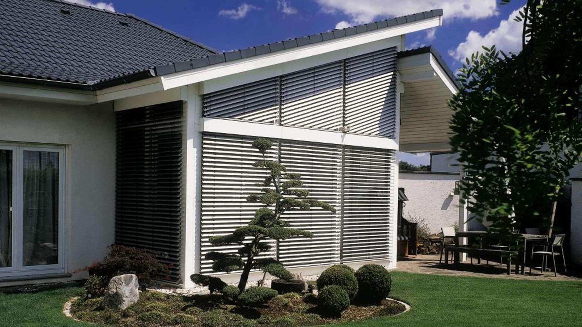 Vorbau mit Pultdach, schrägen Fenstern und Raffstoren davor
