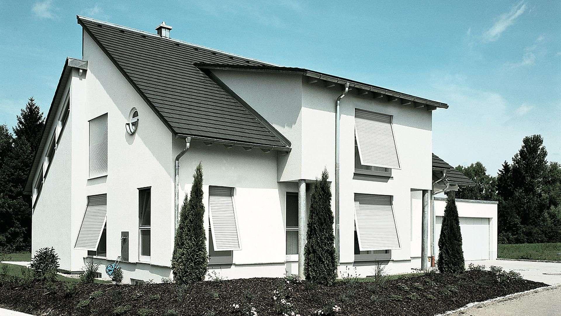 weißes Wohnhaus mit vielen Markisen vor den Fenstern
