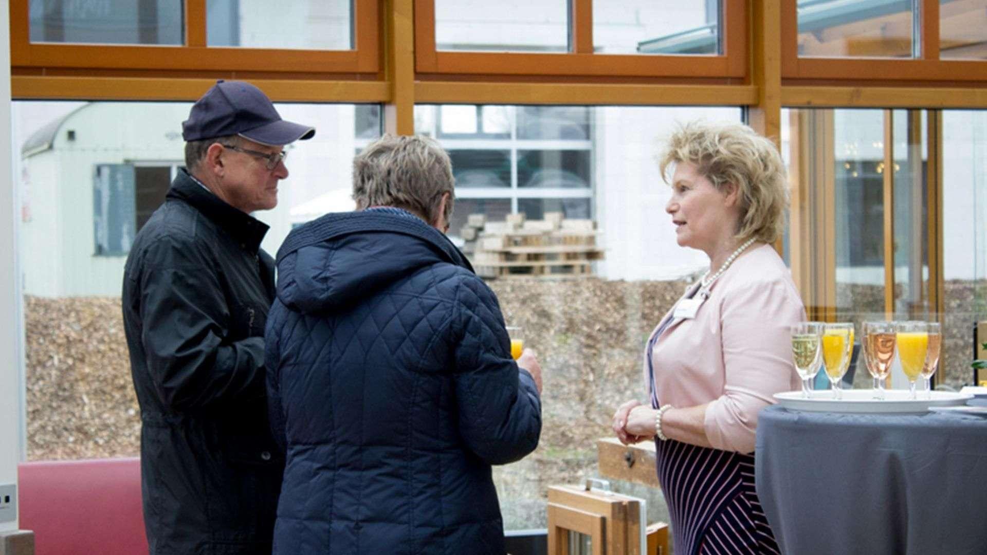 drei Personen trinken Sekt und unterhalten sich in der Ausstellung der Tischlerei Gleue in Lindwedel