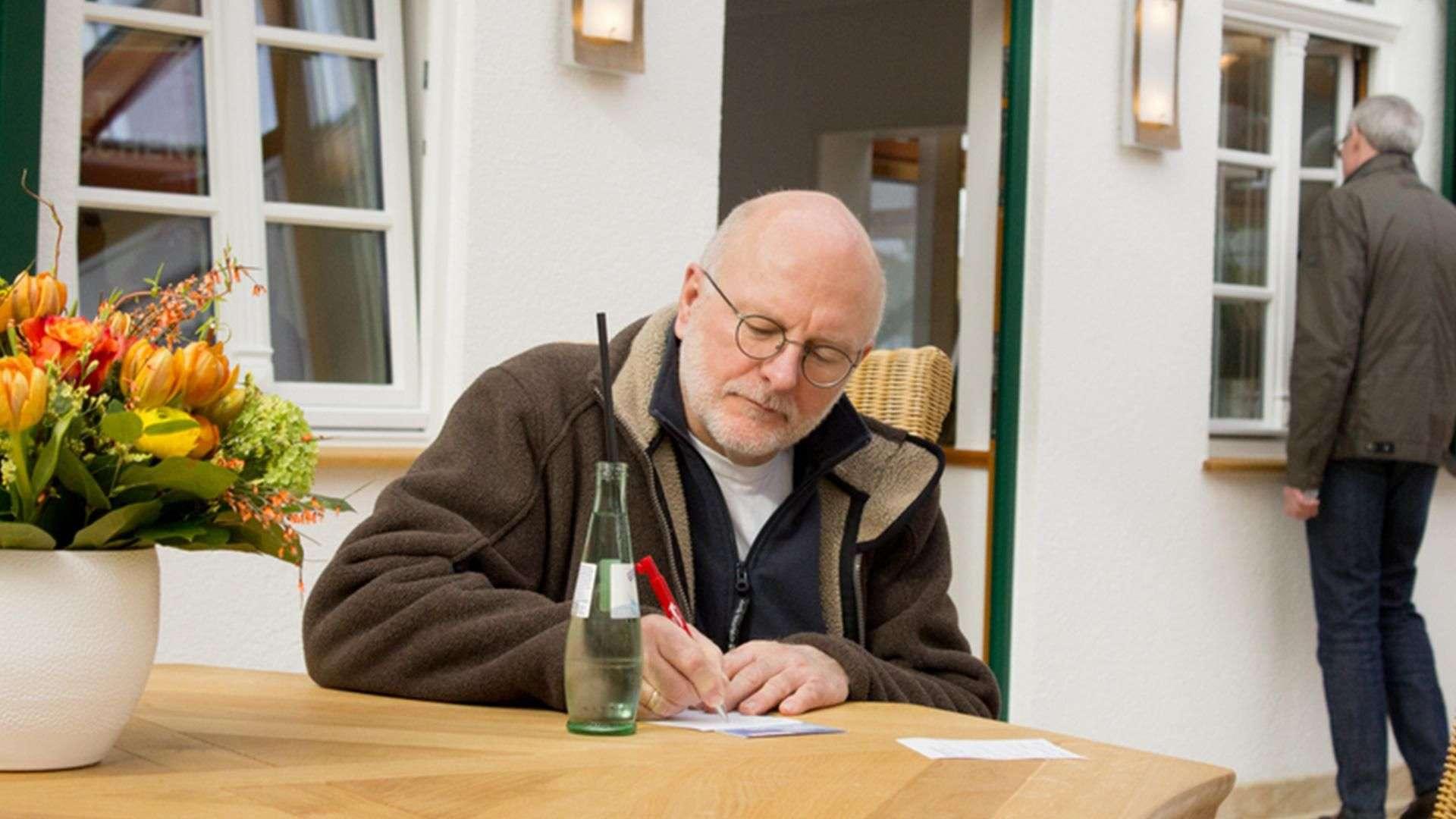 Mann sitzt an einem Tisch und schreibt etwas in der Ausstellung der Tischlerei Gleue in Lindwedel