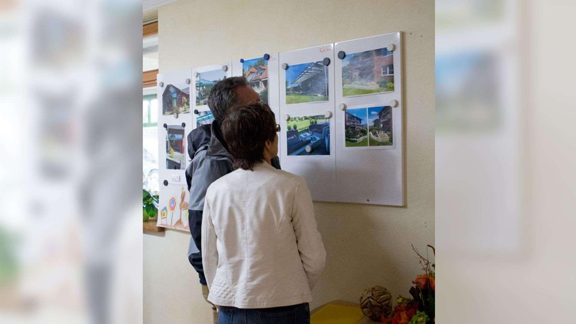 zwei Personen gucken sich in der Ausstellung der Tischlerei Gleue in Lindwedel Bilder an der Wand an