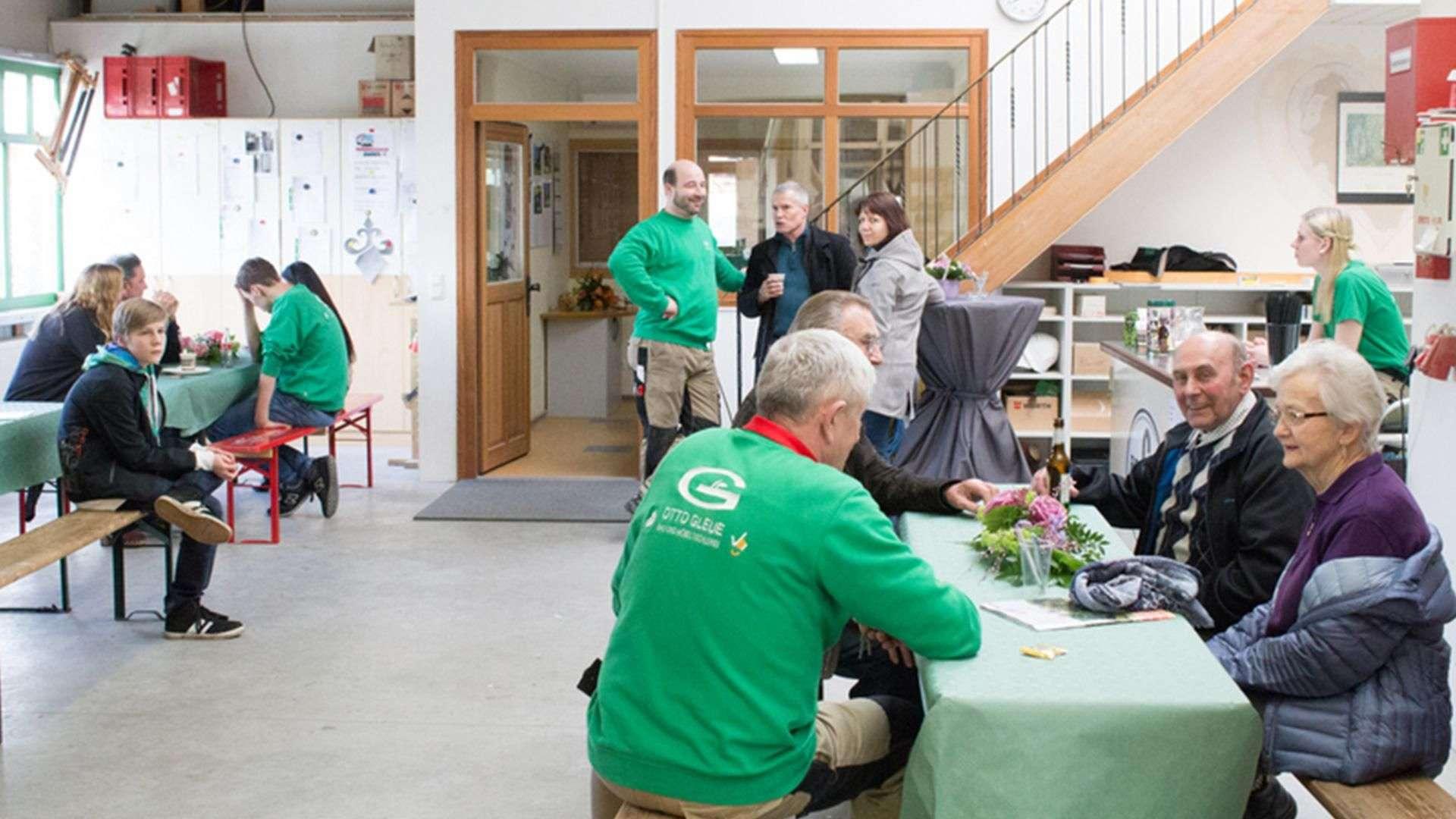 viele Personen sitzen an Tisch in der Ausstellung der Tischlerei Gleue in Lindwedel