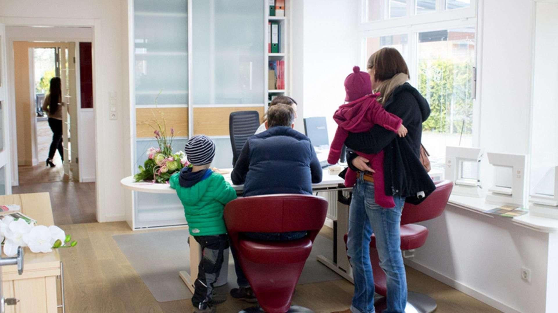 Familie steht vor dem Schreibtisch von Josefine Heinsius