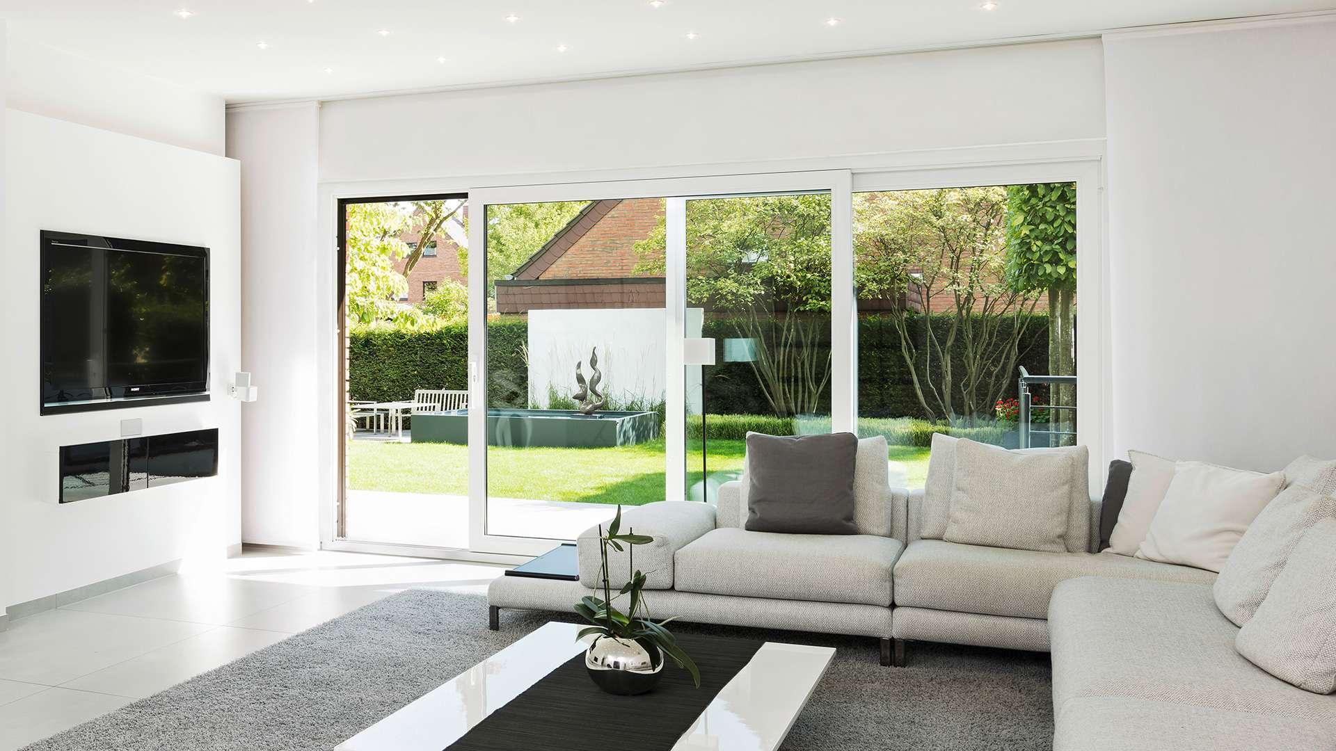 Wohnzimmer mit bodentiefen Schiebefenstern zum Garten