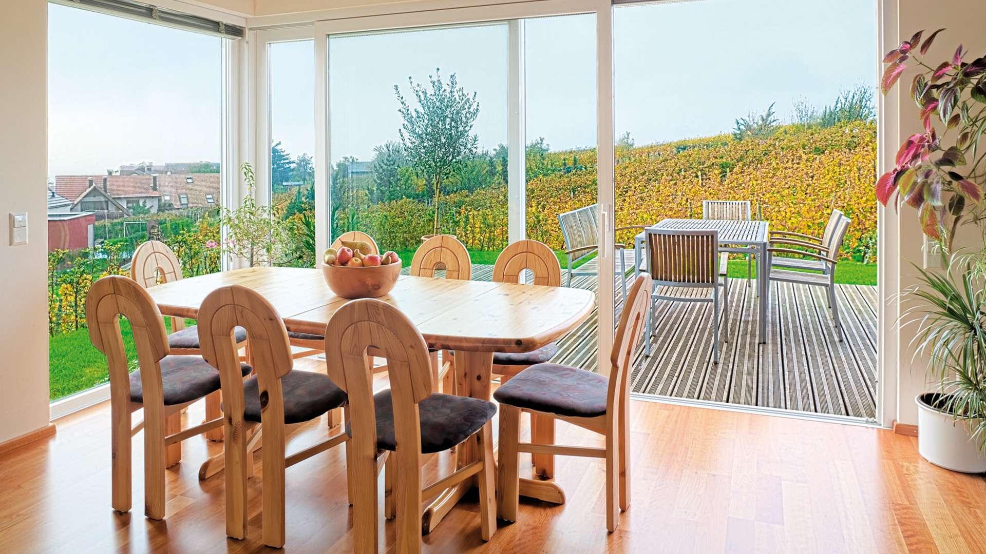 Esszimmer mit bodentiefen Schiebefenstern zur Terrasse