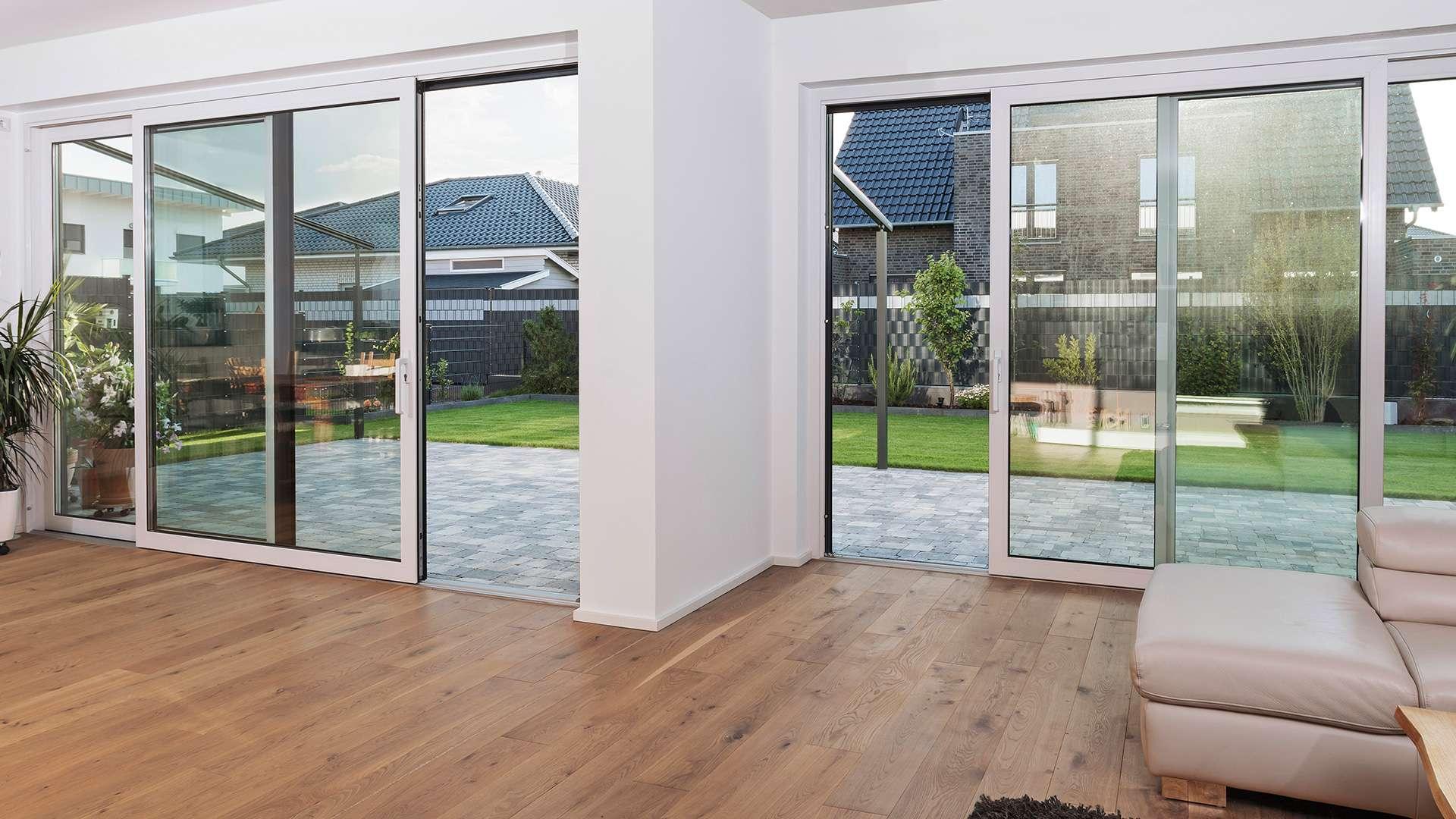 Wohnzimmer mit bodentiefen Schiebefenstern zum Gartn
