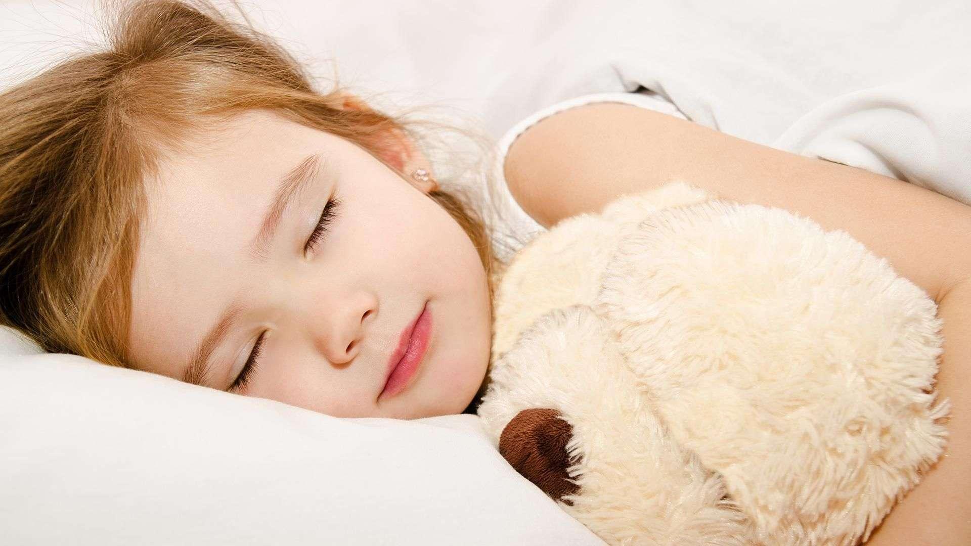 kleines Mädchen schläft mit einem Teddy im Arm