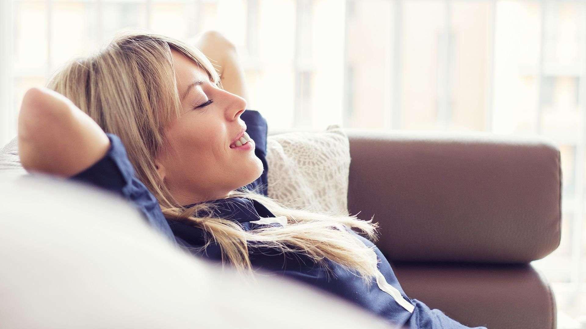 Frau liegt mit geschlossenen Augen und Armen hinter dem Kopf auf dem Sofa