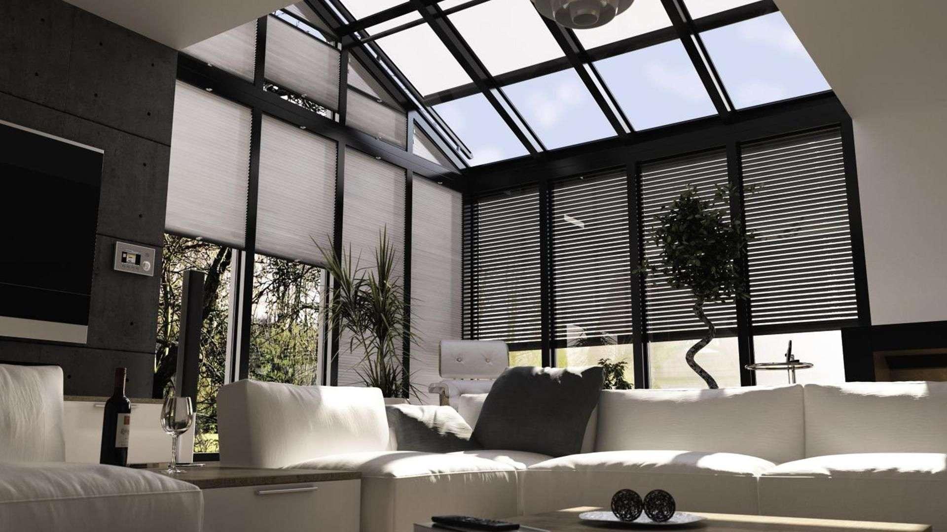Wohnzimmer mit im Dach integrierten Wintergarten mit Textilscreens vor den Fenstern
