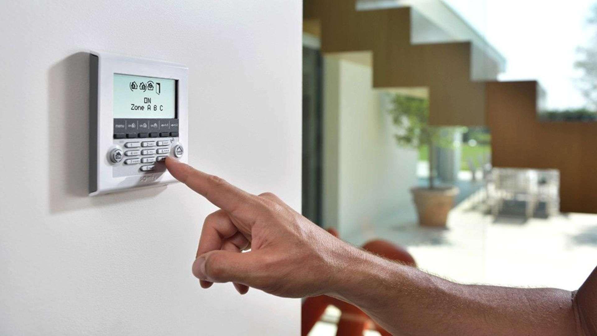 Finger das Steuereinheit des Smart Homes in der Wand bedient