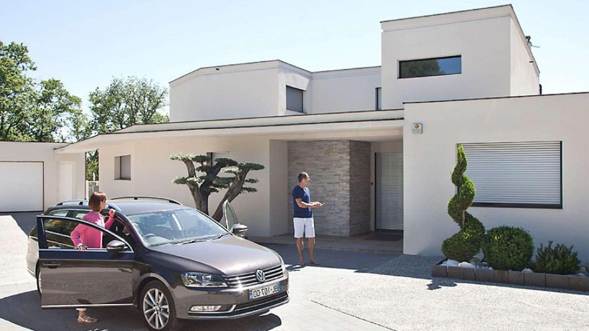 modernes Haus mit Auto davor, wo zwei Personen aussteigen