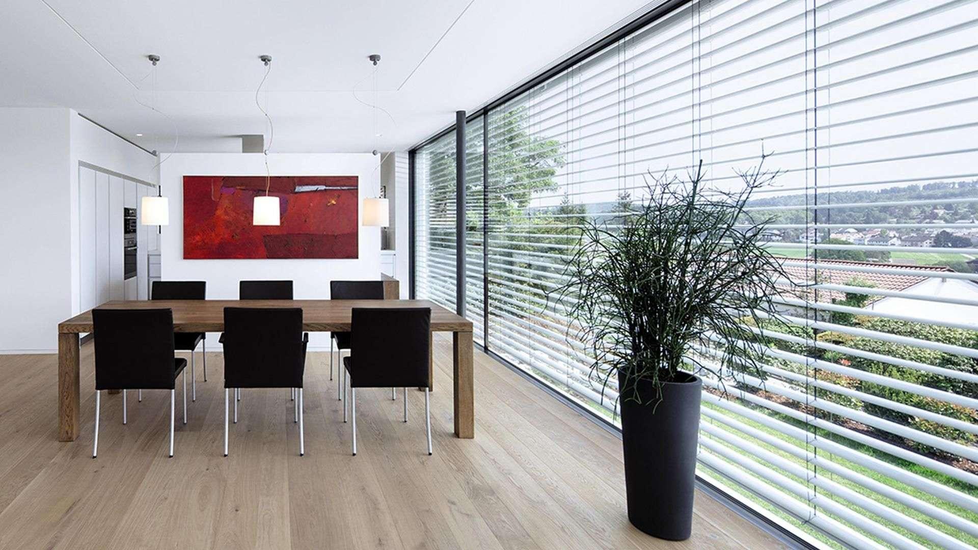 Esszimmer mit langer Glasfront mit Sonnenschutz-Rollo davor