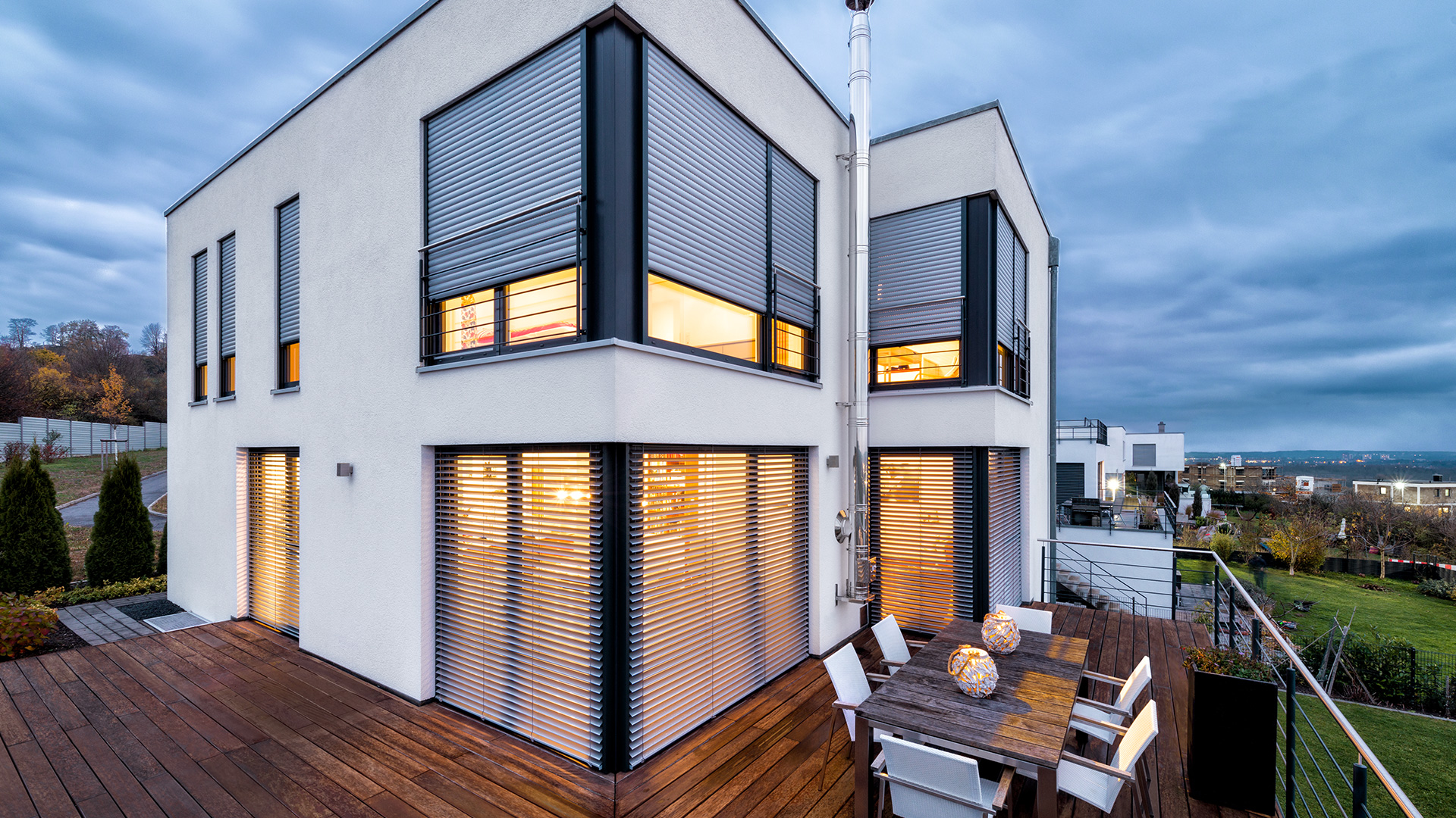 modernes Haus mit Terrasse und Rollläden vor den Fenstern
