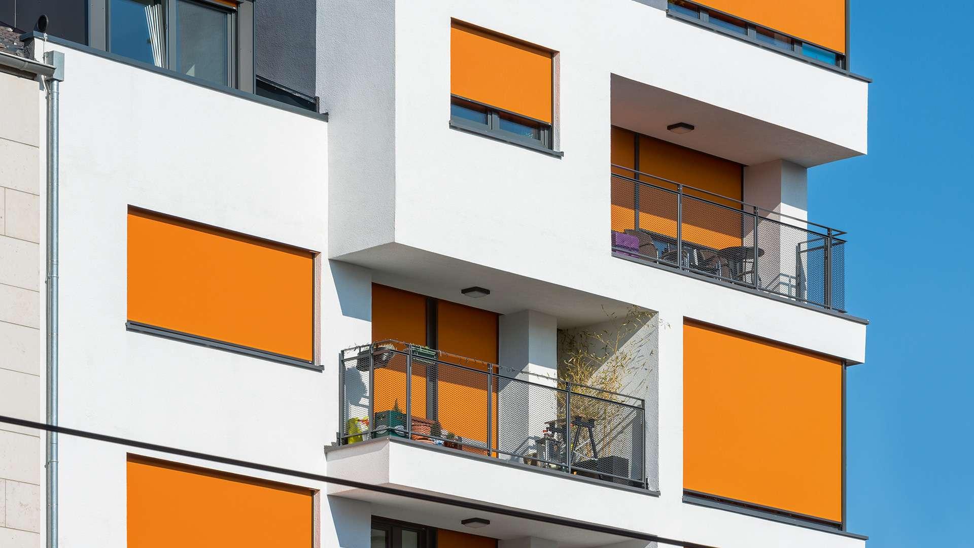 orange Sonnenschutz-Markisen vor den Fenstern eines Mehrfamilienhauses