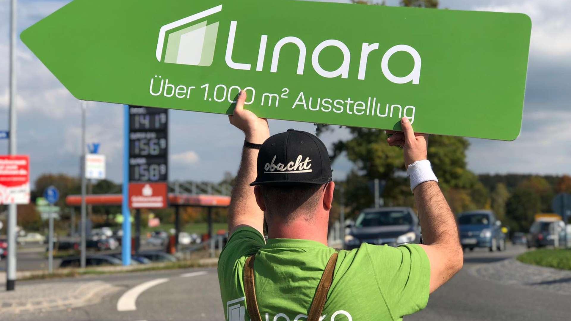 Mann mit Linara-Schild in der Hand