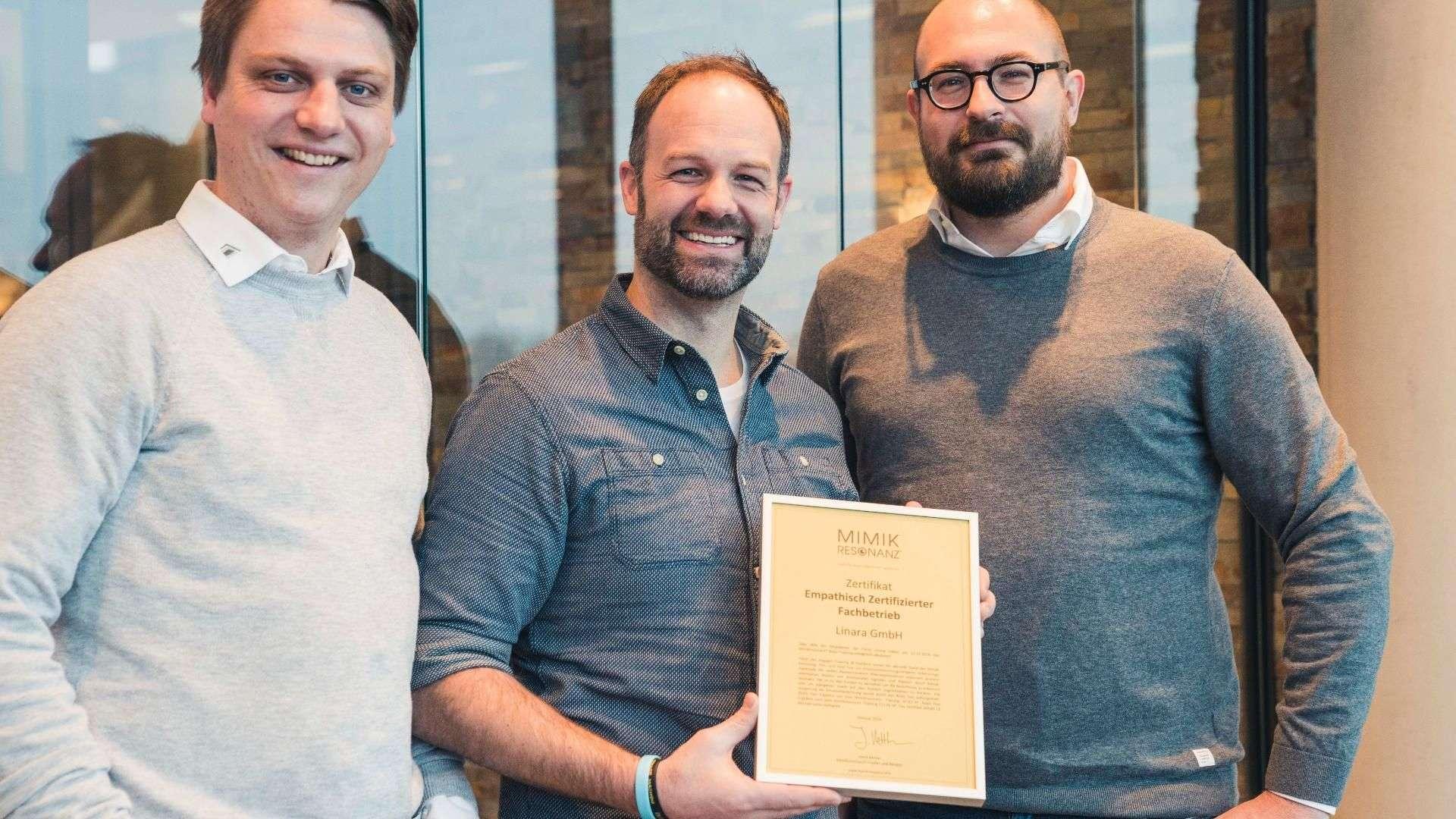 drei Mitarbeiter von Linara mit einem Zertifikat in der Hand