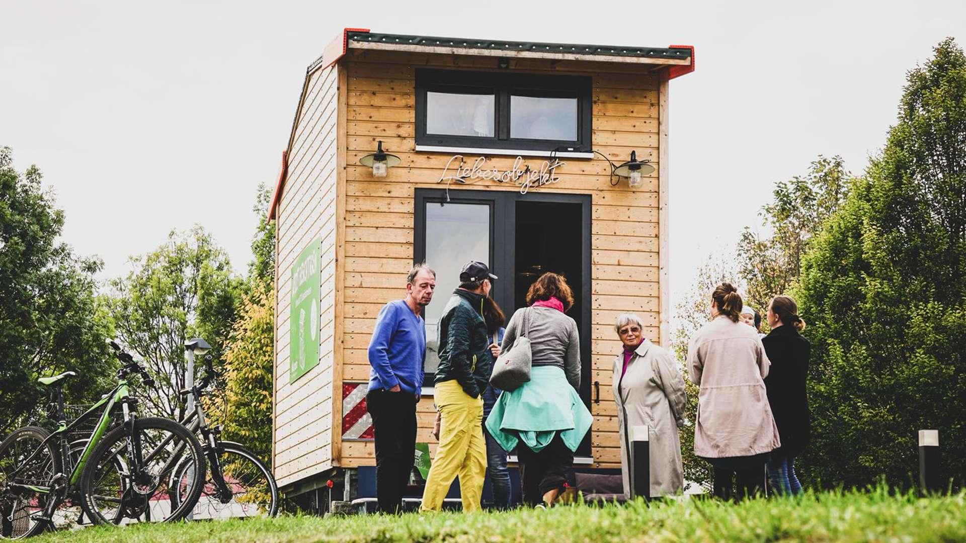 mehrere Personen besichtigen ein Tiny House