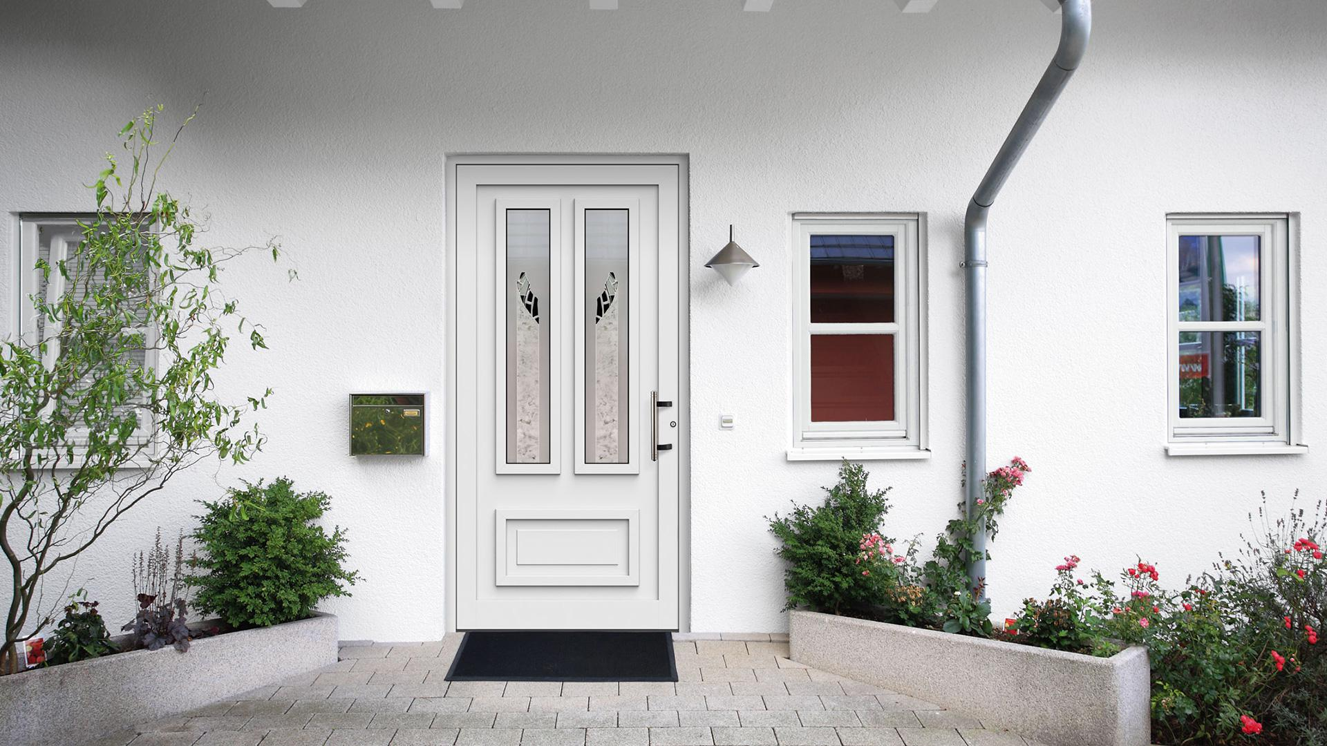 Kompotherm Haustür im Chagall-Design in einer weißen Fassade mit Pflanzen im Eingangsbereich rechts und links
