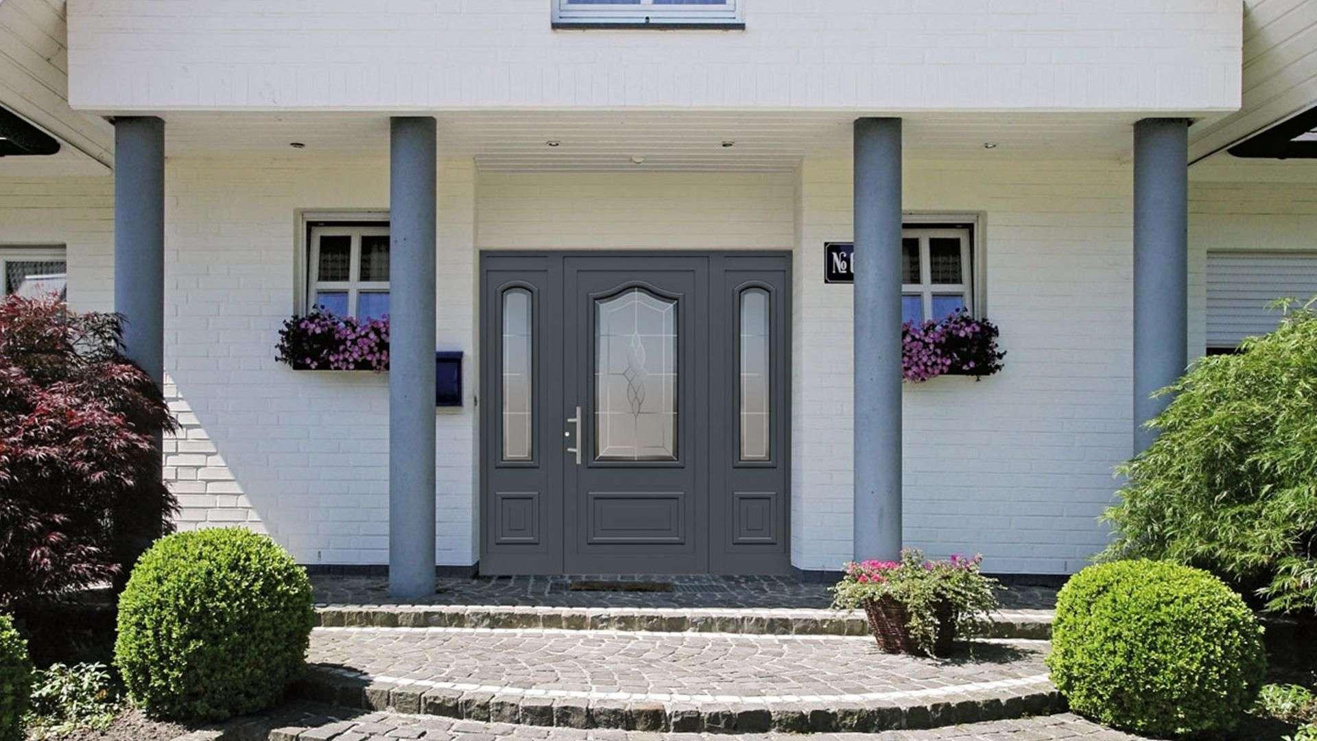 Kompotherm Haustür im Rembrandt-Design in einem weißen Haus mit je zwei grauen Säulen links und rechts