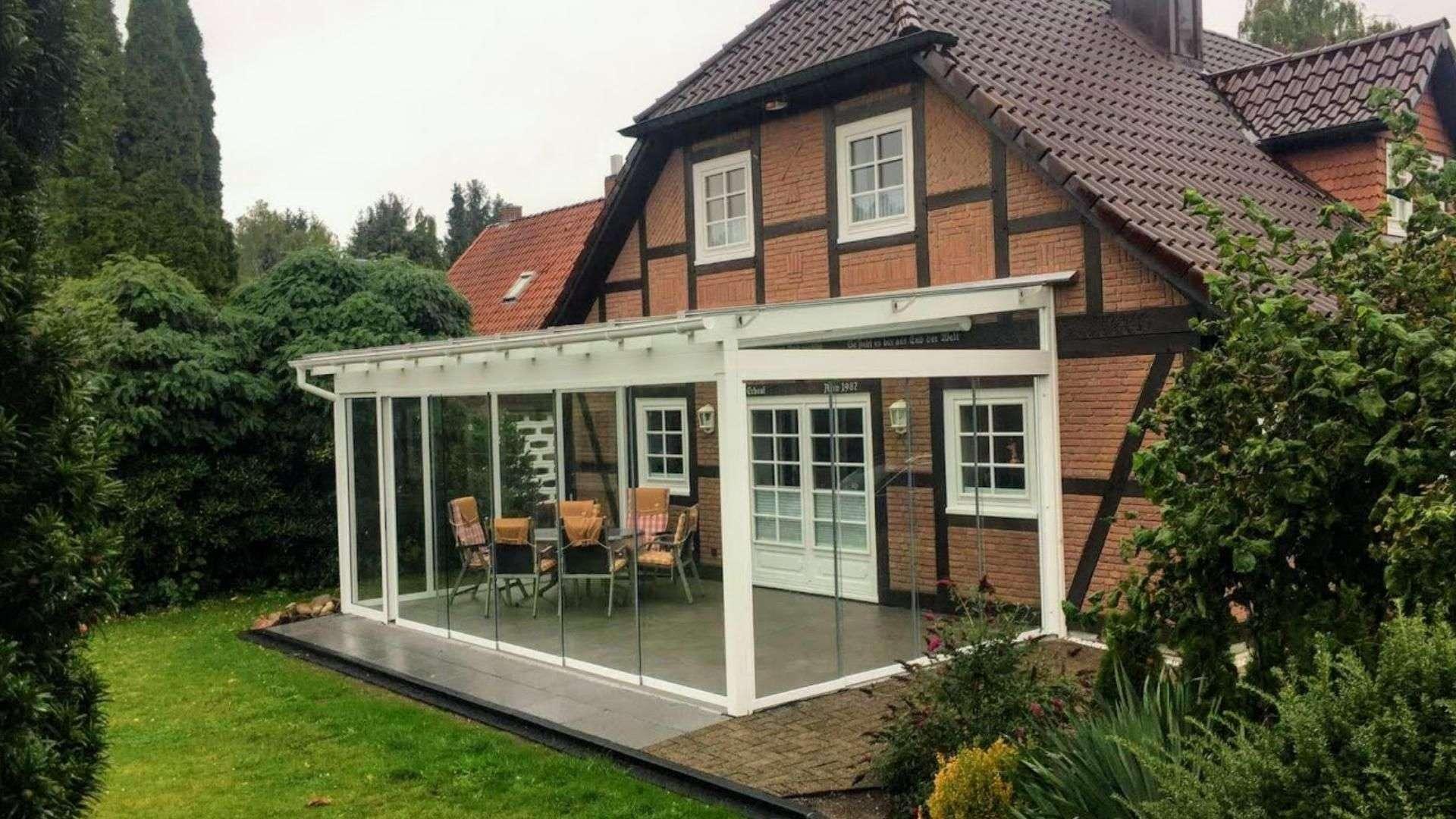 weißes Glashaus an einem Fachwerkhaus