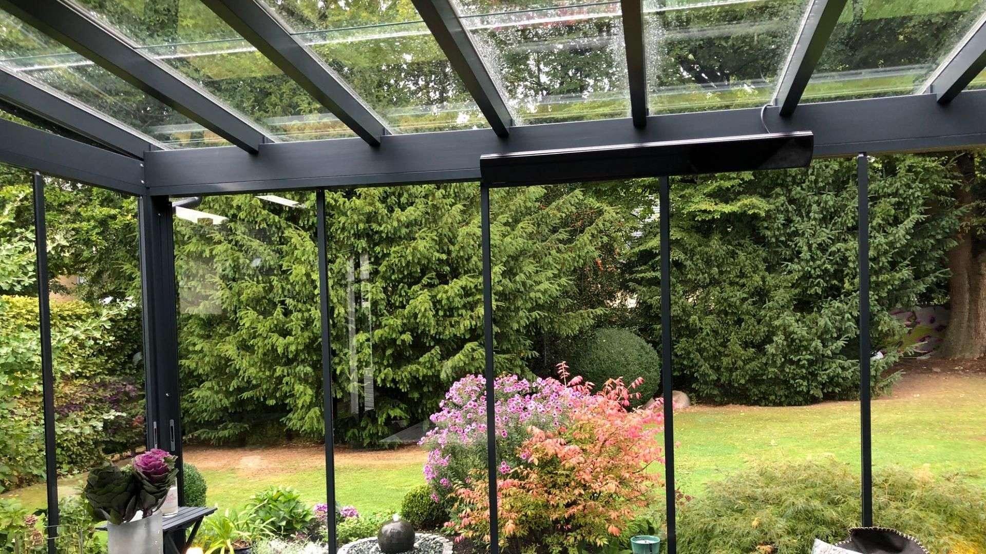 Innenansicht eines Glashauses mit Blick ins Grüne