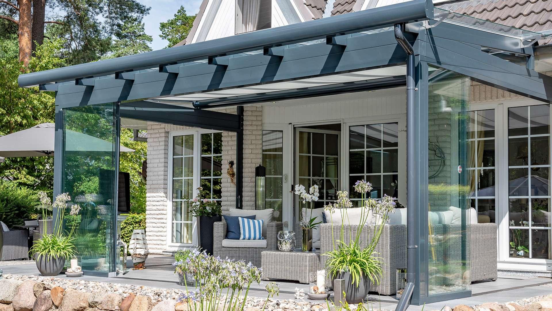 graues Terrassendach an einem weißen Wohnhaus mit moderner Sitzgruppe unter dem Dach