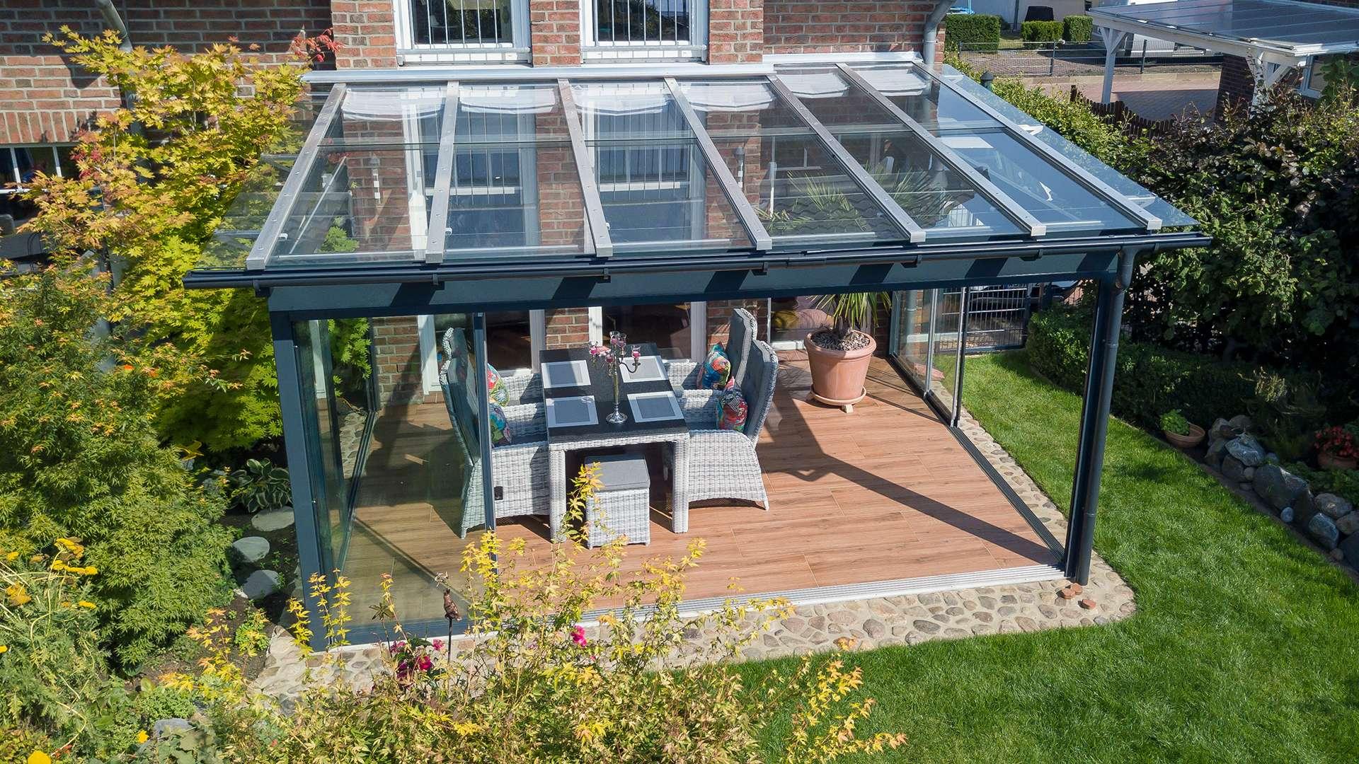 Blick von oben auf ein Terrassendach mit Esstisch auf der Terrasse