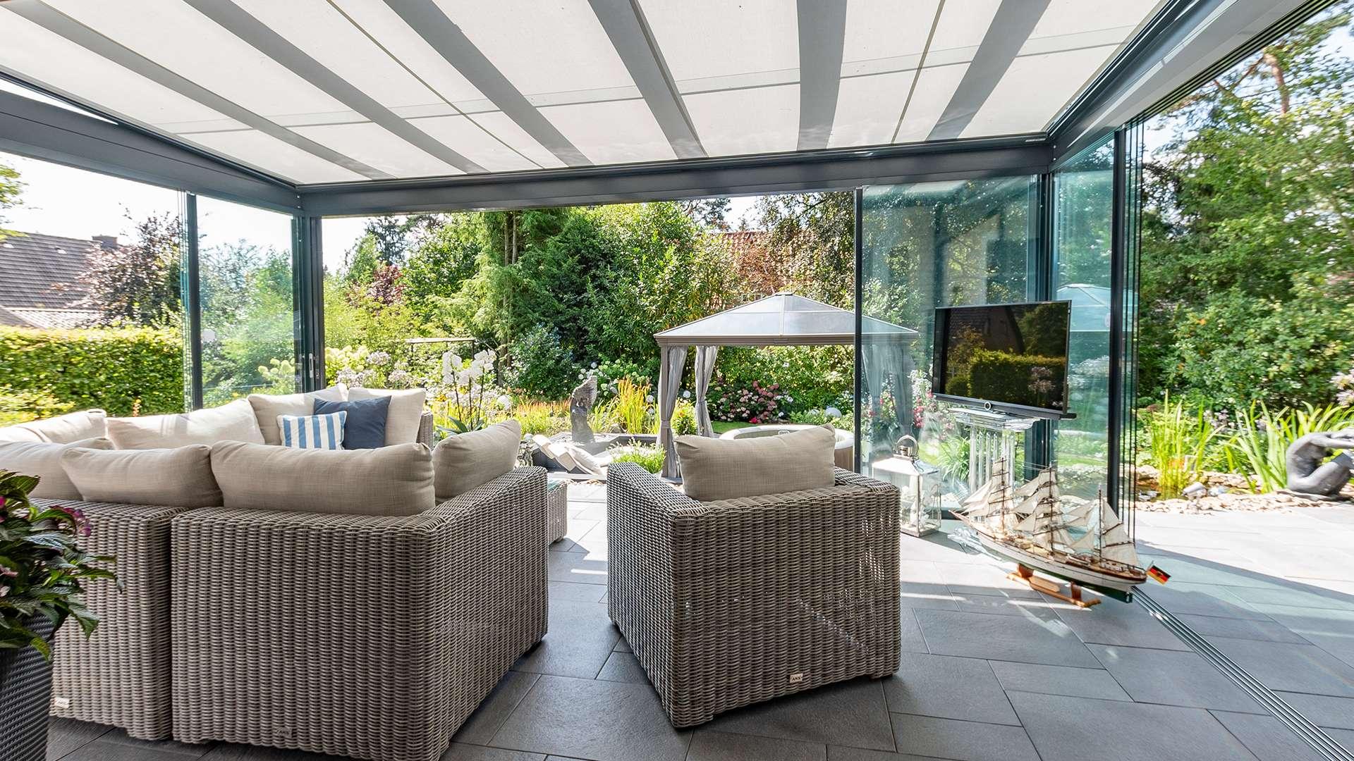Terrassendach mit weißer Unterglasmarkise und moderner Sitzgruppe mit Blick in einen Garten