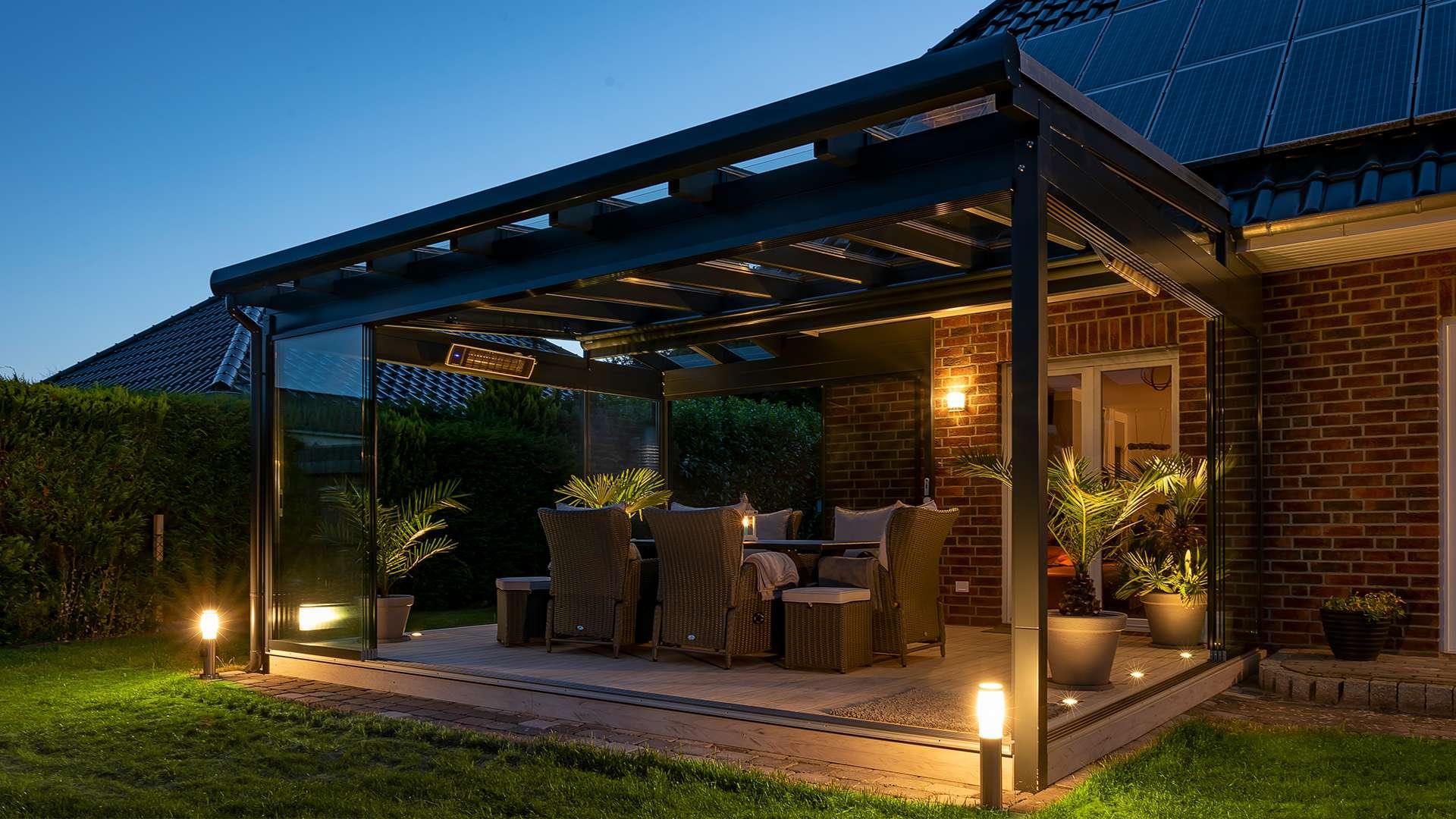 Terrassendach mit Pultdach an einen Wohnhaus bei Nacht. Unter den Terrassendach brennt Licht und ein Esstisch steht auf der Terrasse.