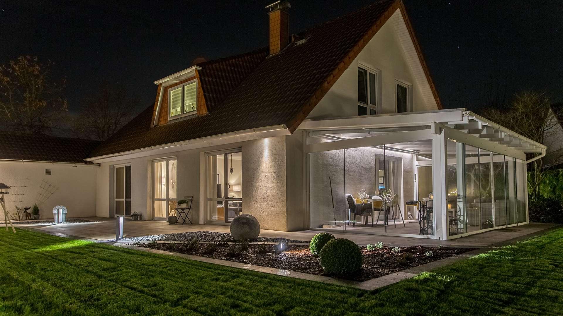 Weißes Wohnhaus mit weißem Wintergarten bei Nacht. Der Wintergarten und die Fenster sind hell erleuchtet.