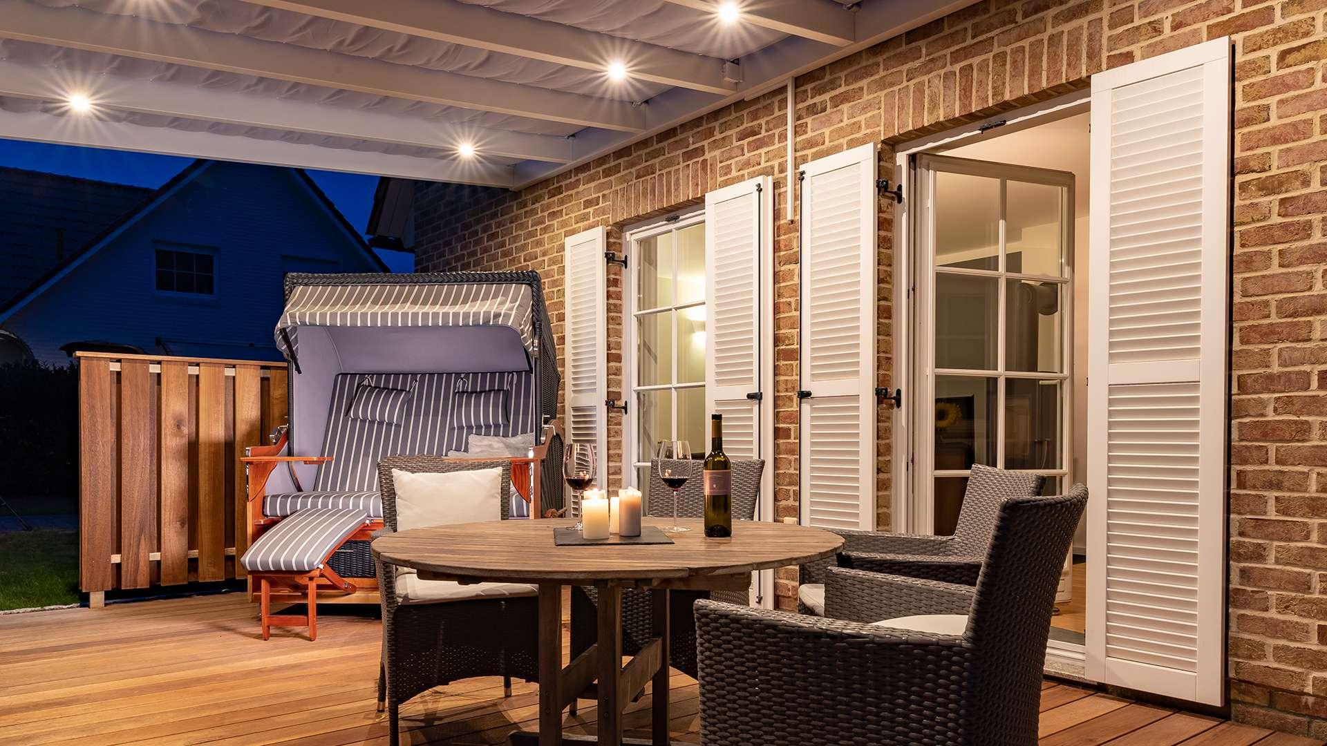 Blick unter ein beleuchtetes Terrassendach mit Esstisch und Strandkorb