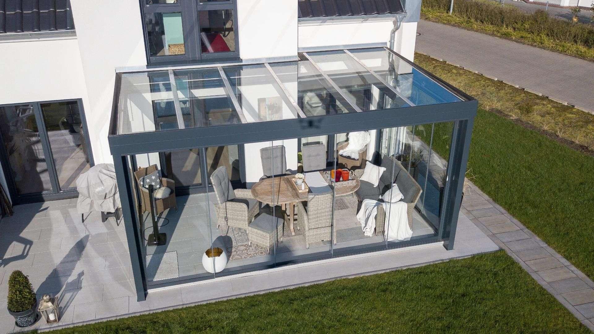 Glashaus an einem weißen Wohnhaus