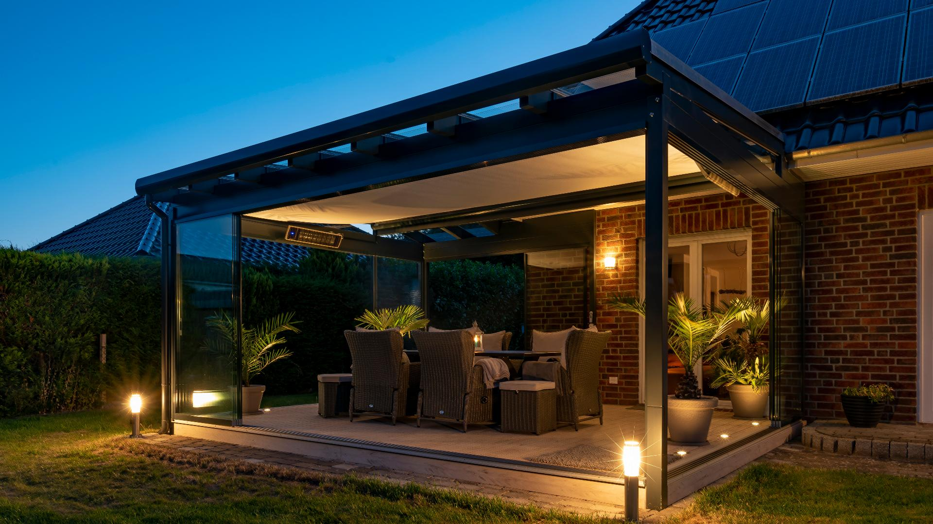 beleuchtetes Glashaus an einem Einfamilienhaus bei Nacht