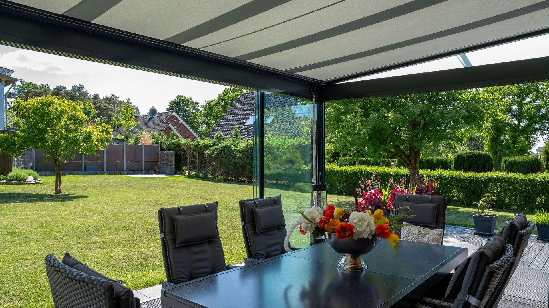 Innenansicht eines Glashauses mit Unterglasmarkise mit Blick in den Garten