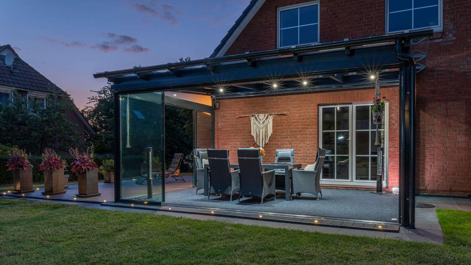 beleuchtetes Glashaus auf der Terrasse eines Einfamilienhauses