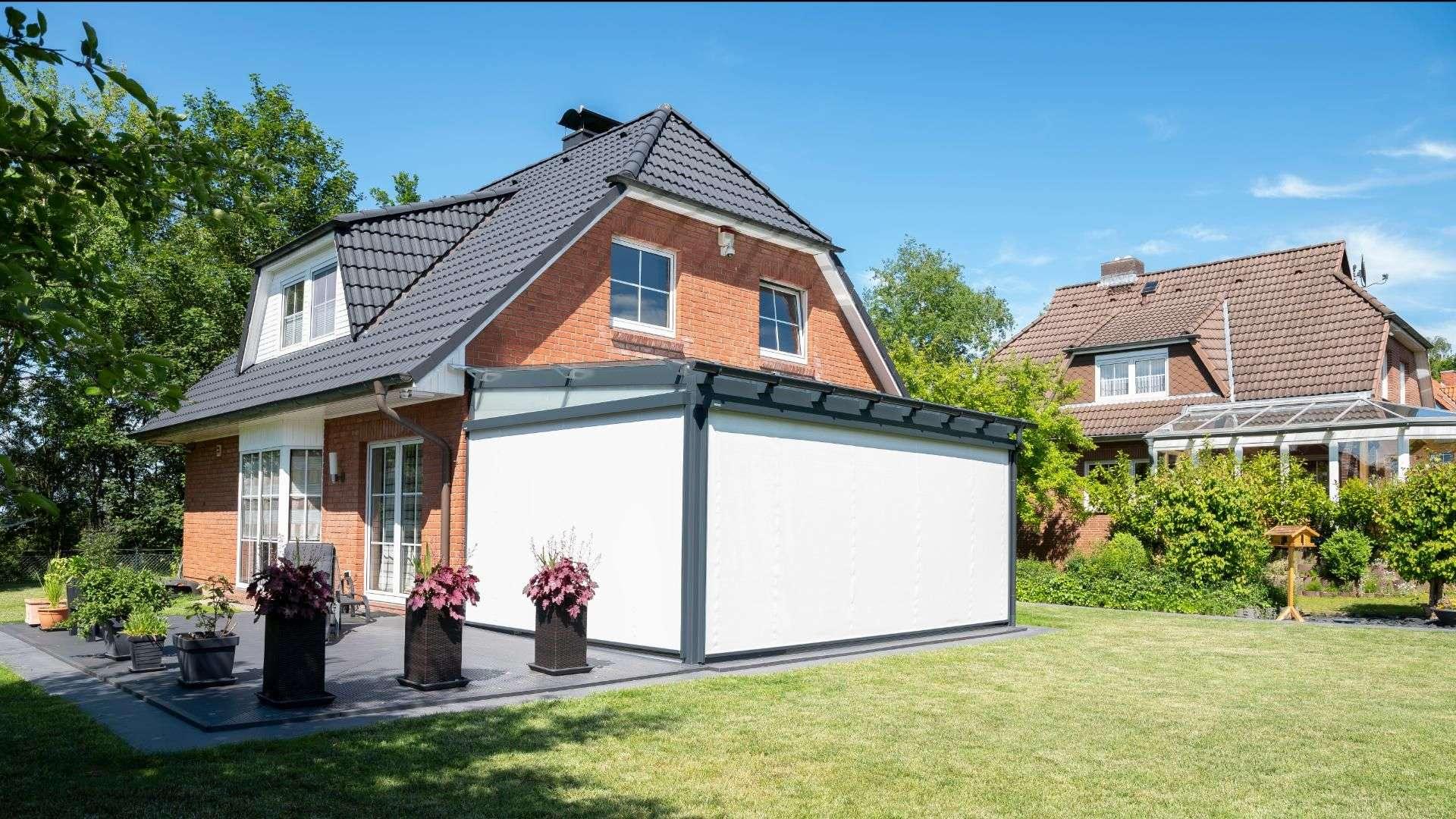Glashaus mit Vertikalmarkisen an einem Einfamilienhaus