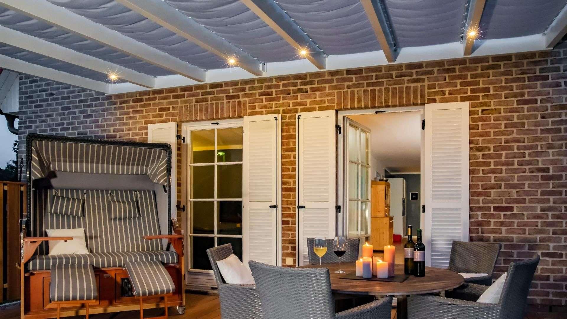Blick unter ein Terrassendach mit LED-Lichtern. auf der Terrasse steht ein runder Tisch mit fünf Stühlen und ein Strandkorb.