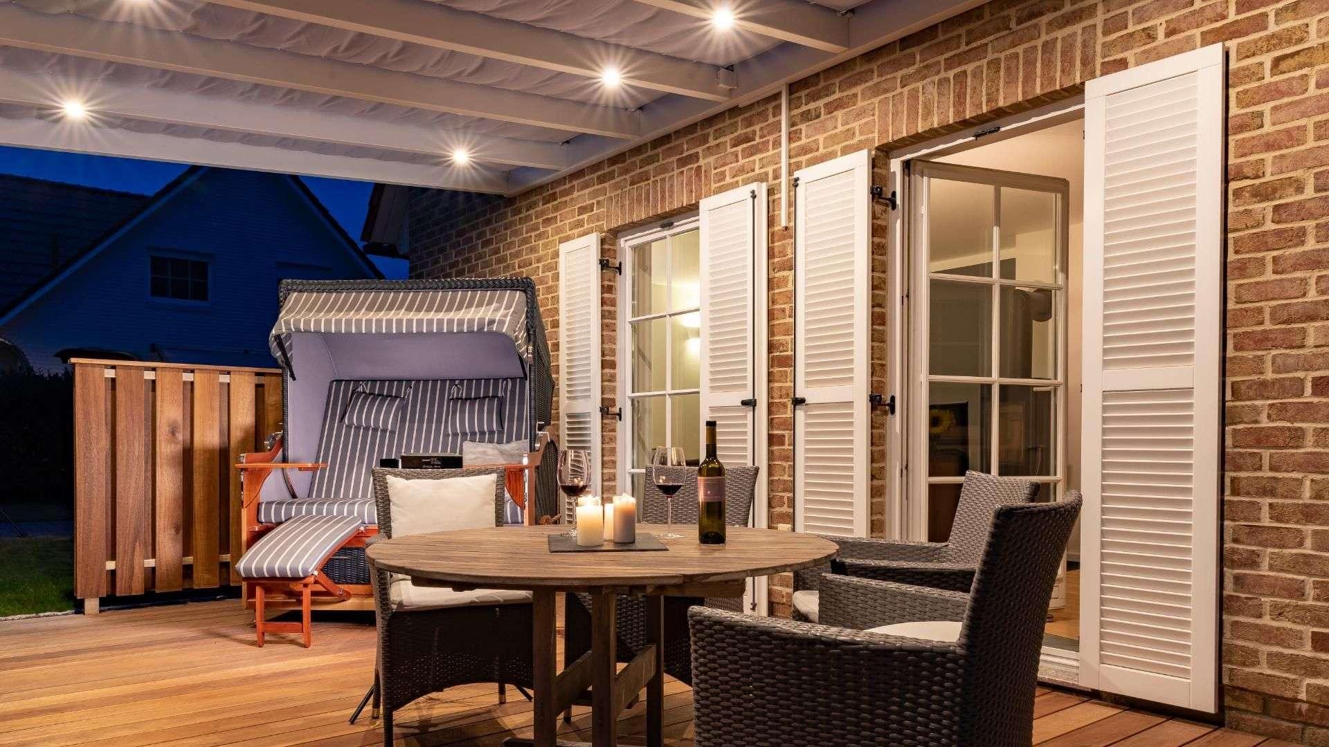 Innenansicht eines beleuchteten Terrassendachs mit Esstisch und Strandkorb