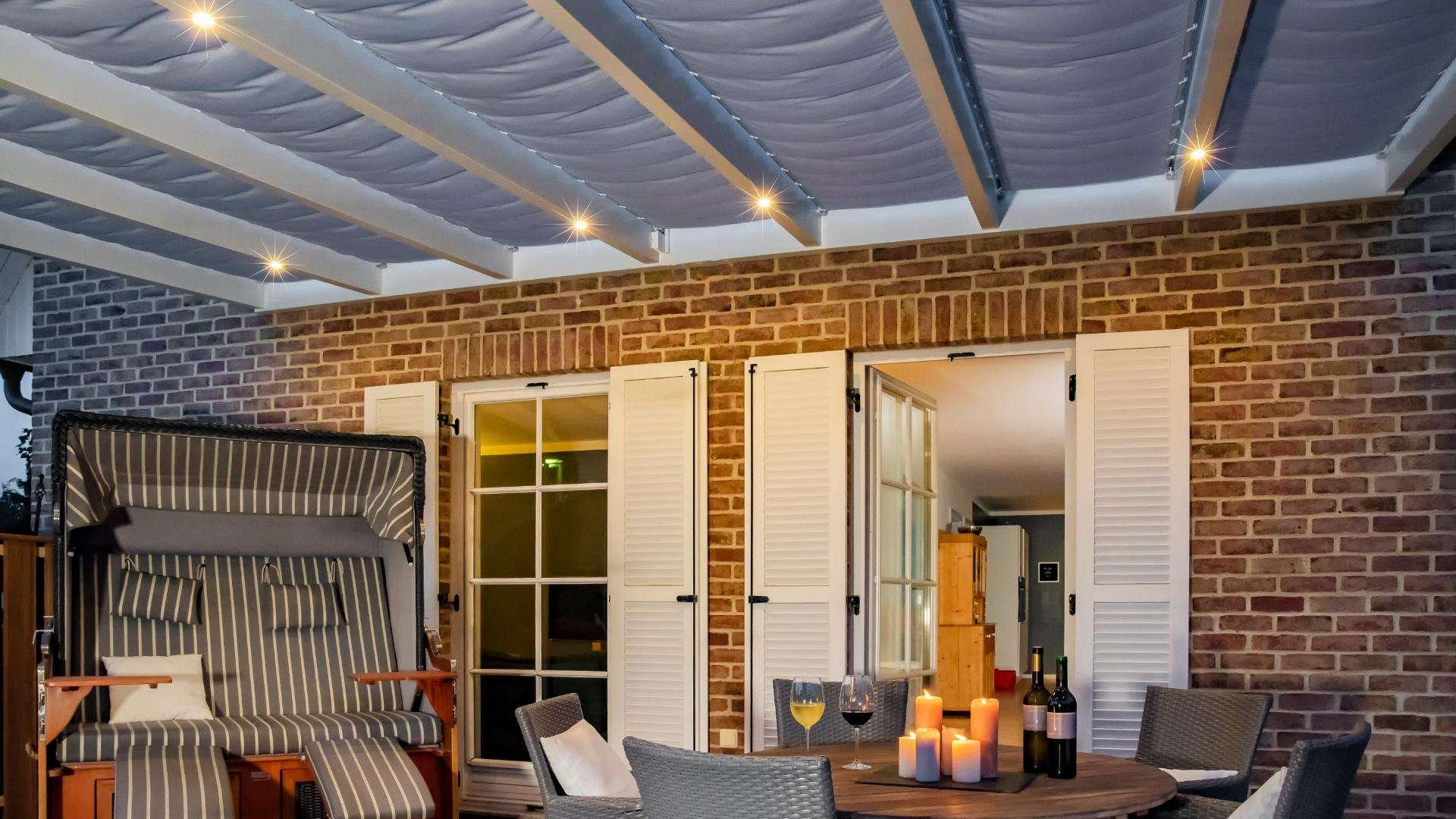 Innenansicht eines beleuchtetes Terrassendachs mit Esstisch und Strandkorb