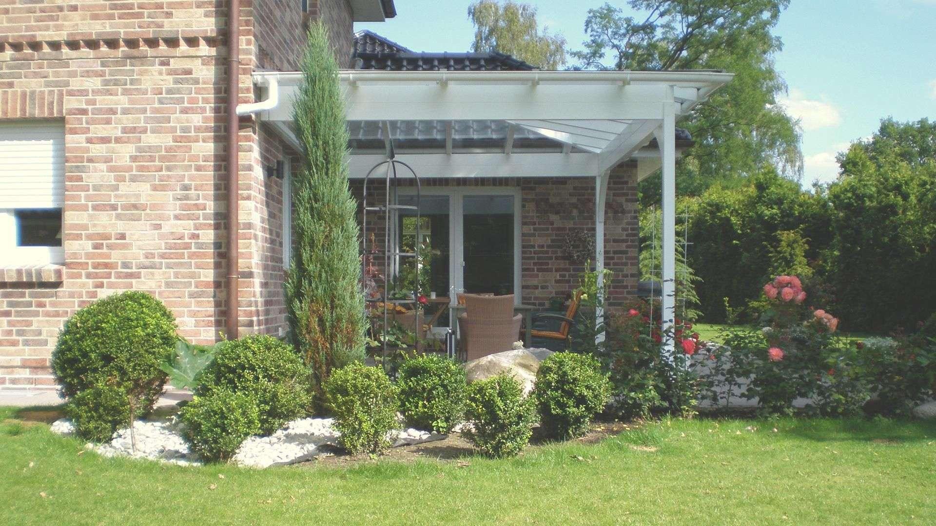 weißes Terrassendach an einem großen Haus mit großen Garten