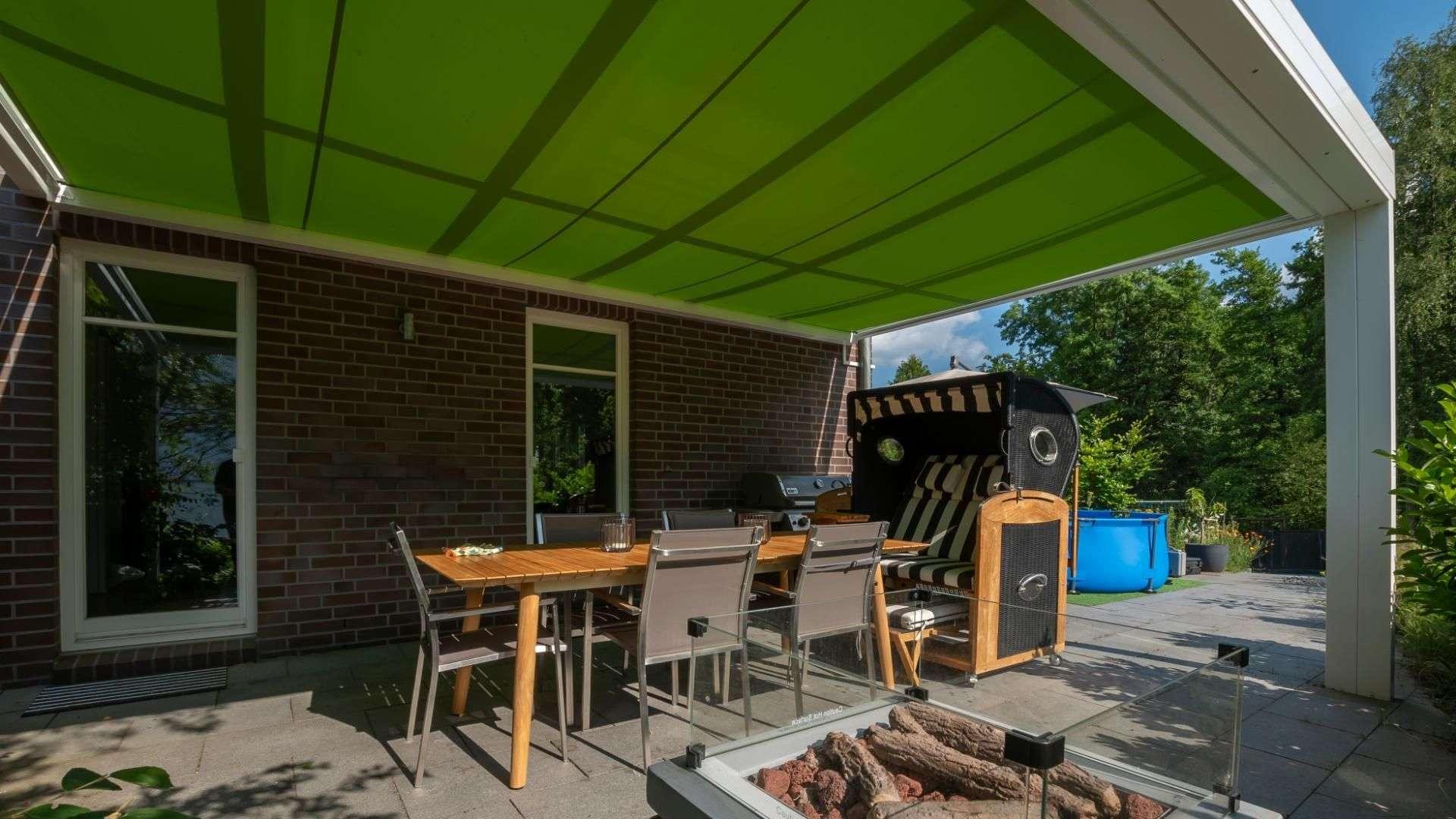 grüne Unterglasmarkise unter einem weißen Terrassendach mit Esstisch und Strandkorb
