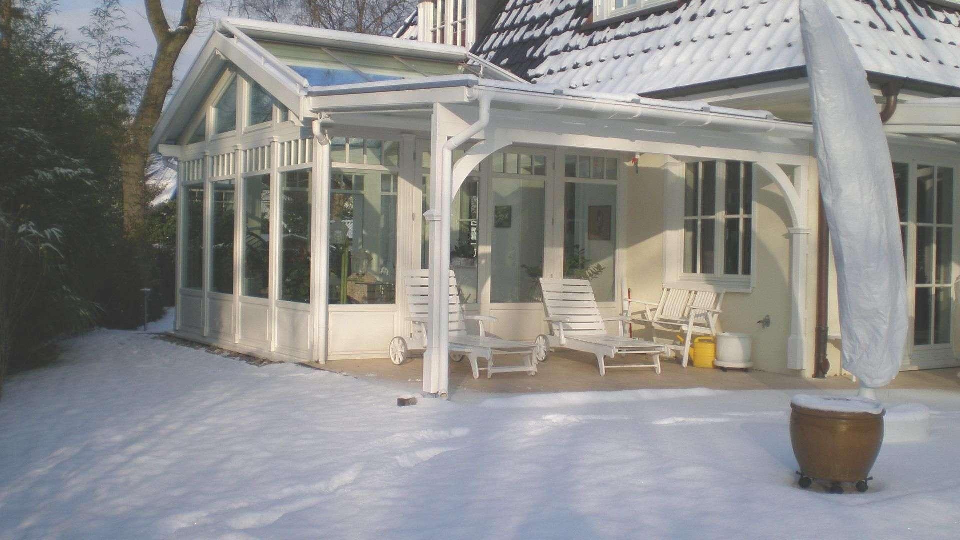 Wintergarten mit Flügeldach an einem Wohnhaus mit schneebedecktem Garten