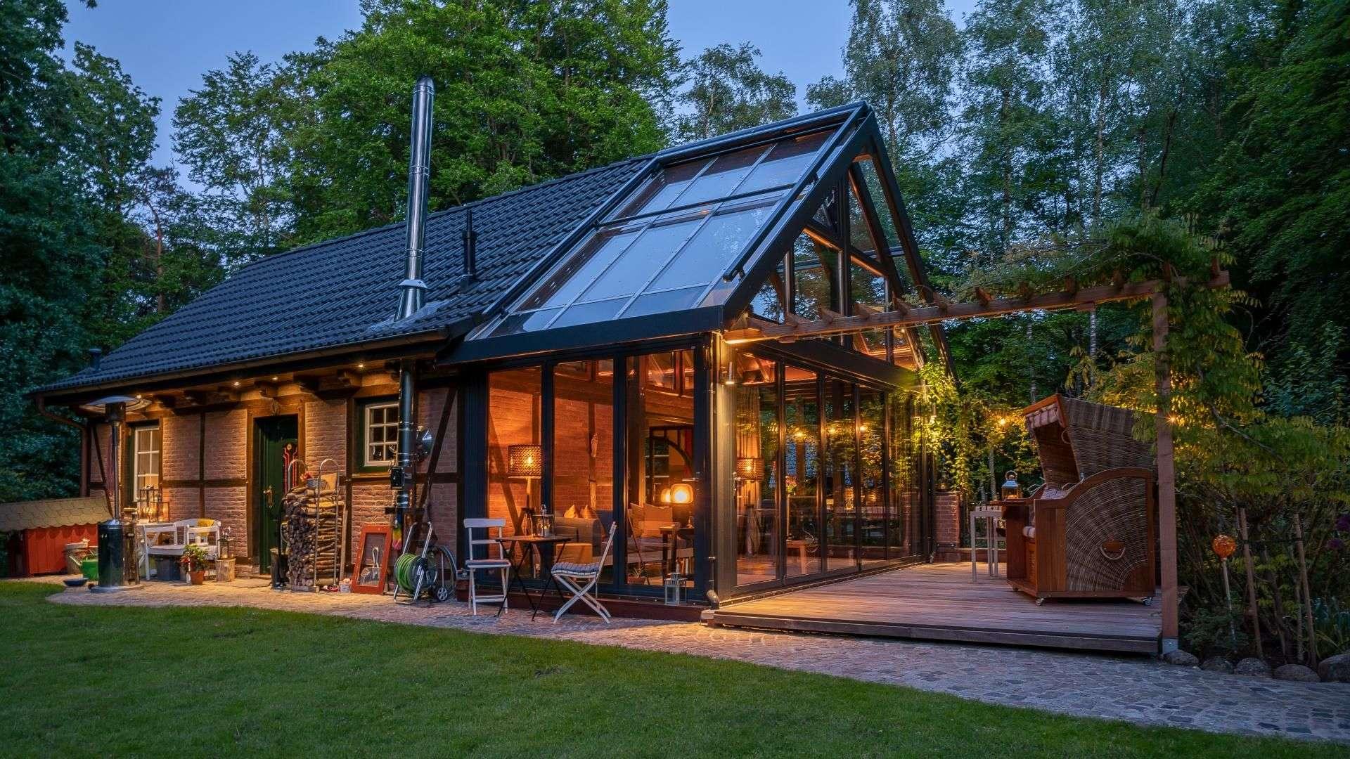 beleuchteter Wintergarten an einem Fachwerkhaus