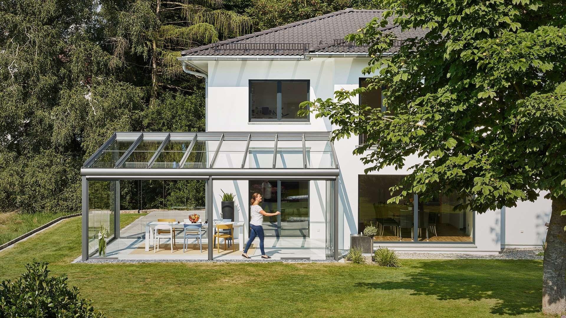 Glashaus an einem Wohnhaus mit Garten im Grünen