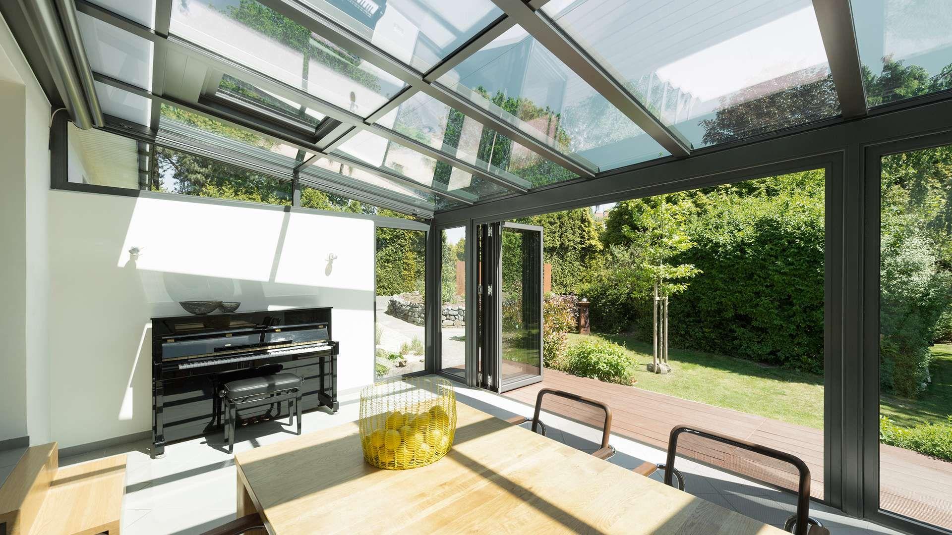 Innenansicht eines Wintergartens mit Esstisch und Klavier