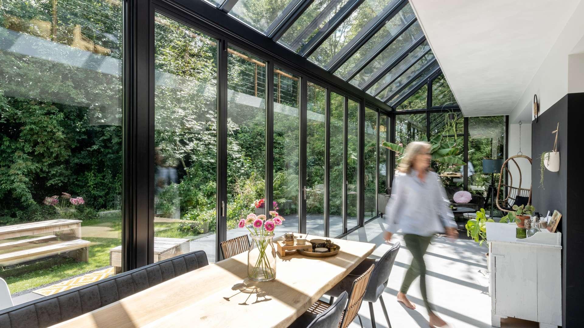 langer Wintergarten mit Esstisch und Blick ins Grüne