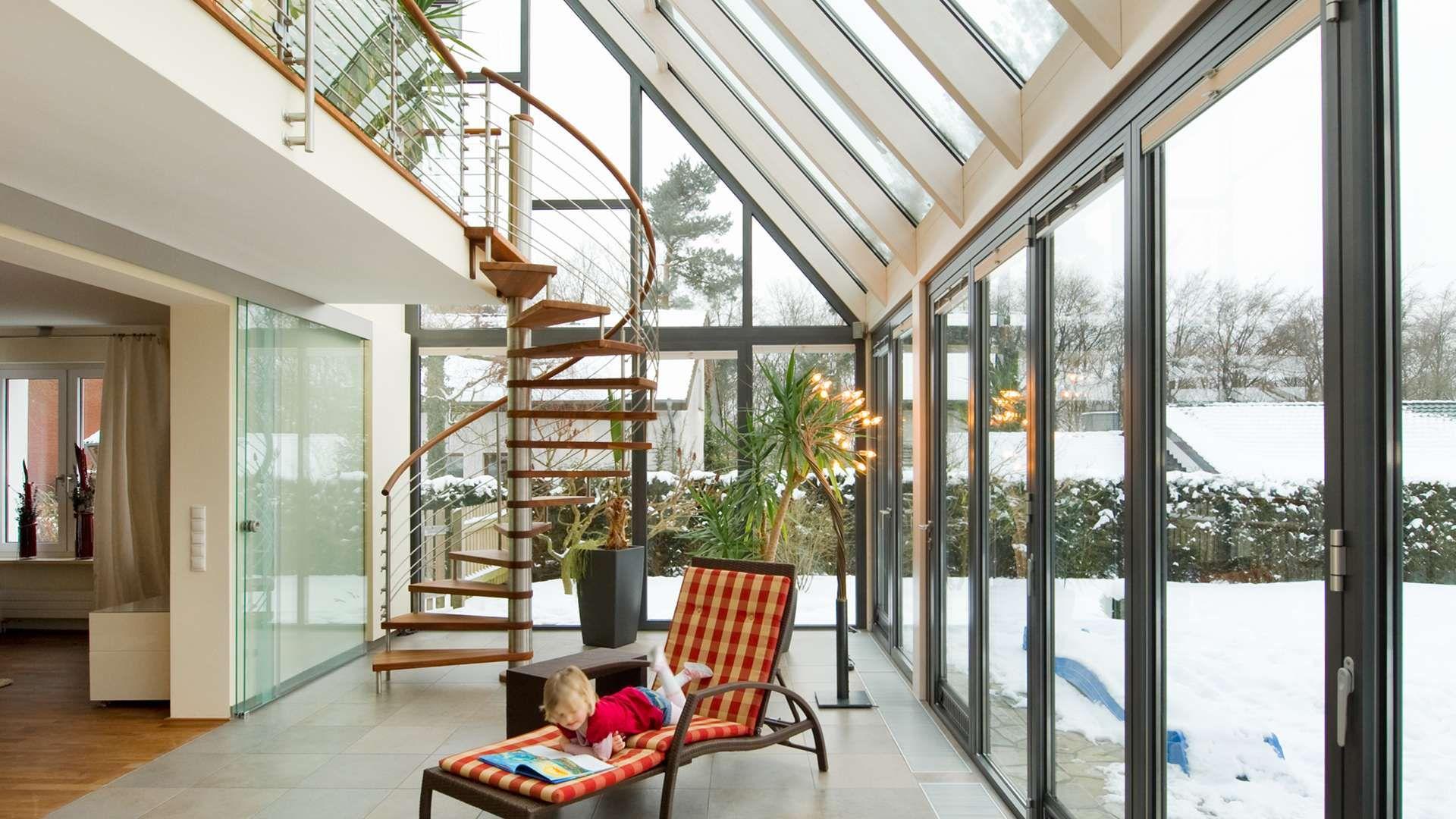 Innensansicht eines Wintergartens mit Wendeltreppe und Sonnenliege auf der ein Kind liegt