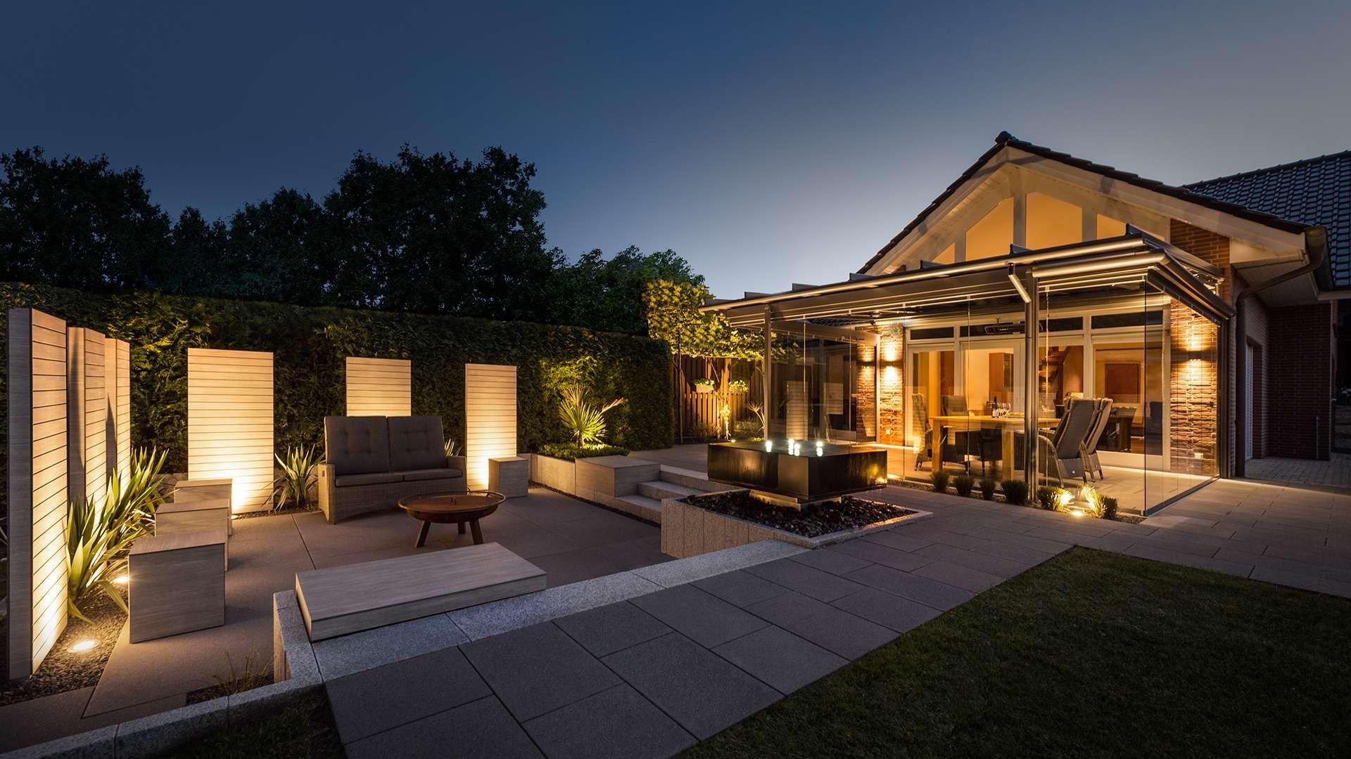 Wohnhaus mit Terrassendach und großer Terrasse bei Nacht