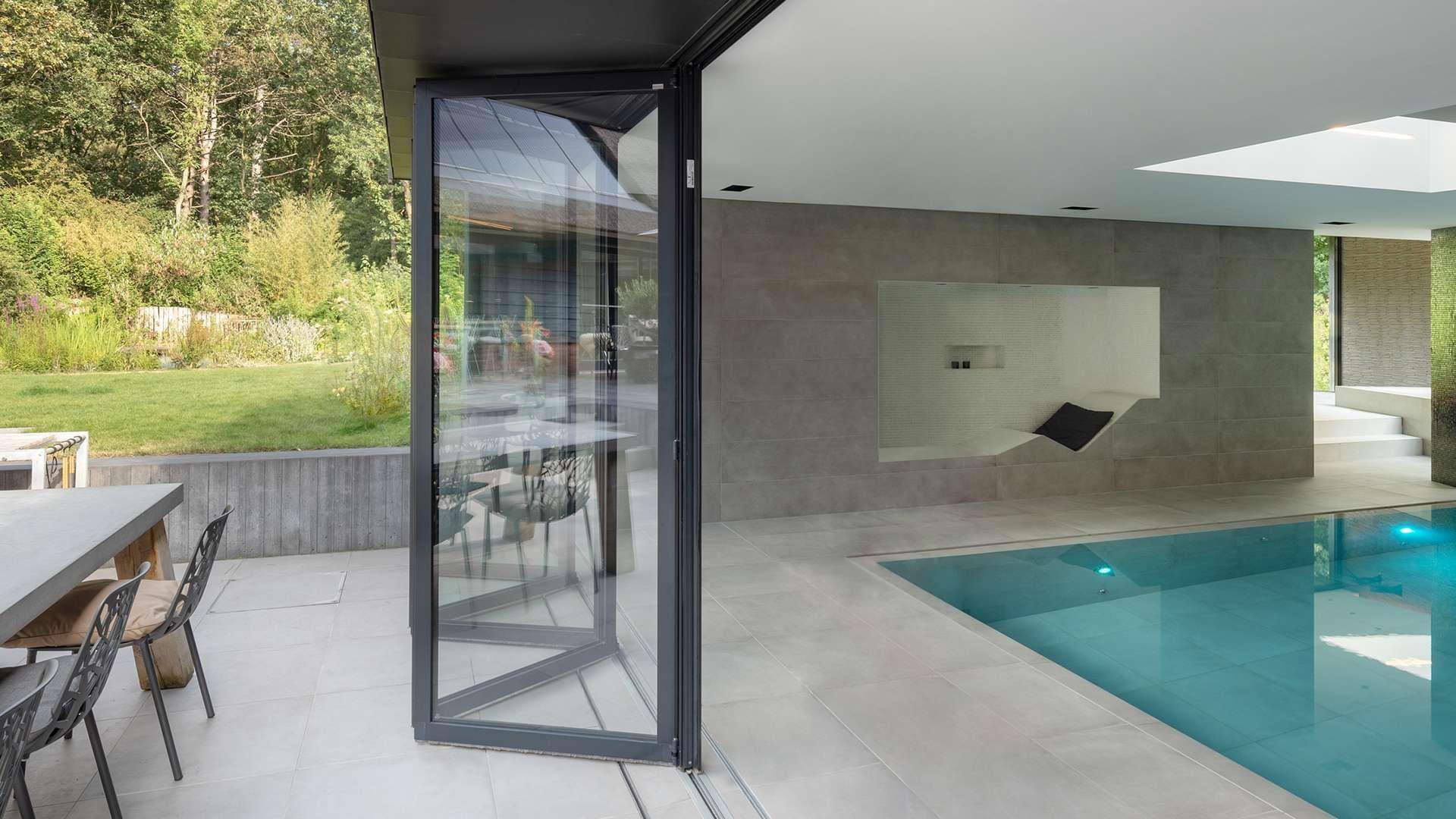 geöffnete Glas-Faltwand zwischen Indoor-Pool und Terrasse