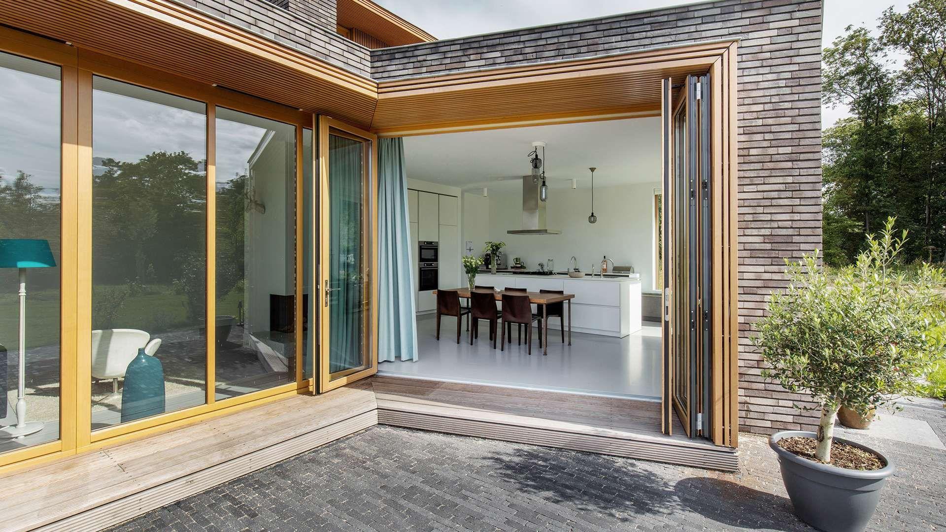 geöffnete Glas-Faltwand aus Holz mit Blick in eine Küche